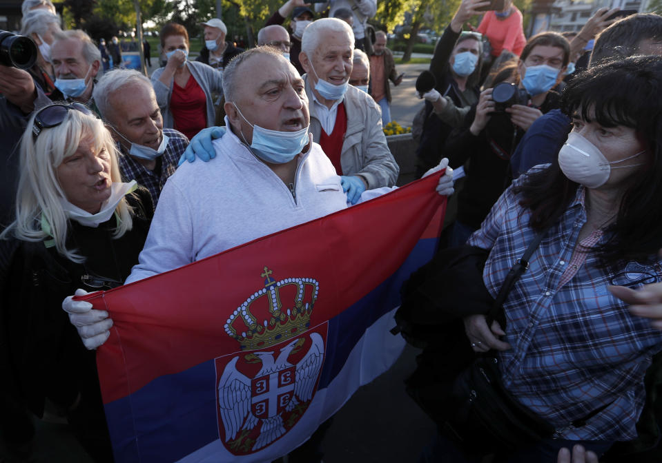 Government supporters hold a Serbian flag and shout slogans during a Serbian opposition leaders protest in front of the Serbian parliament building in Belgrade, Serbia, Thursday, April 30, 2020. Serbian opposition leaders gathered during an evening curfew to protest measures imposed by the populist authorities against the spread of the new coronavirus. Serbia's populist government in mid-March introduced some of the harshest measures in Europe, banning people over 65 years old from leaving their homes and imposing a daily and weekend curfews. (AP Photo/Darko Vojinovic)