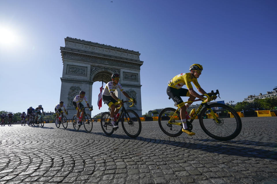 Slovenia's Tadej Pogacar, wearing the overall leader's yellow jersey, passes the Arc de Triomphe during the twenty-first and last stage of the Tour de France cycling race over 108.4 kilometers (67.4 miles) with start in Chatou and finish on the Champs Elysees in Paris, France,Sunday, July 18, 2021. (AP Photo/Daniel Cole)