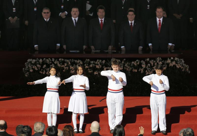 Children sign the national anthem during the swearing-in ceremony for new President Horacio Cartes at Palacio de Lopez presidential palace in Asuncion, Paraguay, Thursday, Aug. 15, 2013. The men standing behind are, from left, Supreme Court President Antonio Fretes, Congress President Juan Ramirez, Senate President Julio Velazquez, Paraguay's new President Horacio Cartes and his Vice President Juan Afara. (AP Photo/Jorge Saenz)