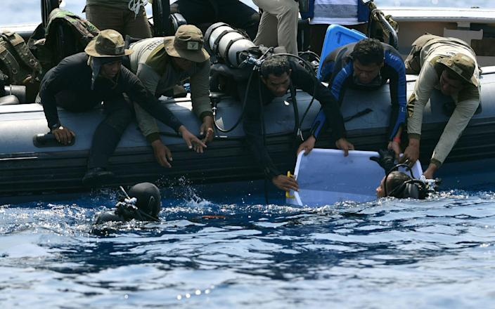 An Indonesian Navy diver holds a recovered