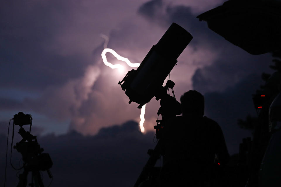 A bolt of lightning illuminates the evening sky as astrophotographer Johnny Horne waits to photograph Comet NEOWISE at Grandfather Mountain in Linville, N.C., Friday, July 17, 2020. (AP Photo/Gerry Broome)