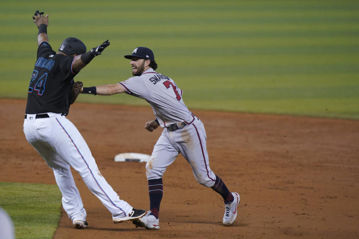 Atlanta Braves shortstop Dansby Swanson (7) runs down Miami Marlins' Jesus Aguilar (24) during a double play in the third inning of a baseball game, Saturday, June 12, 2021, in Miami. Marlins' Corey Dickerson was out at first. (AP Photo/Wilfredo Lee)
