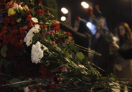 People lay flowers near fence of Kazan airport, where Tatarstan Airlines Boeing 737-500 airliner crashed