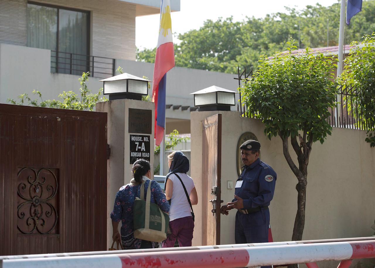 People visit the embassy of the Philippines where a national flag is at half-mast mourning the reported death of Ambassador Domingo Lucenario, Jr. in Islamabad, Pakistan, Friday, May 8, 2015. The ambassadors to Pakistan from the Philippines and Norway and the wives of the ambassadors from Malaysia and Indonesia were killed Friday when a Pakistani army helicopter carrying foreign dignitaries made a crash landing in the country's north, the military said. (AP Photo/B.K. Bangash)