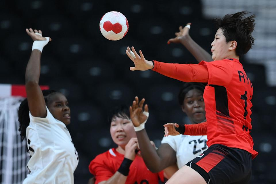 <p>South Korea's right back Ryu Eun-hee (R) passes the ball during the women's preliminary round group A handball match between South Korea and Angola of the Tokyo 2020 Olympic Games at the Yoyogi National Stadium in Tokyo on August 2, 2021. (Photo by Franck FIFE / AFP)</p>