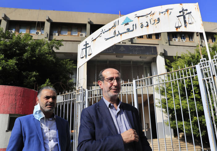 Hezbollah legal representative Ibrahim Mussawi, right, walks outside the justice ministry as he arrives to speak with journalists in Beirut, Lebanon, Friday, Dec. 4, 2020. Lebanese Hezbollah said on Friday it is suing a former Christian lawmaker and a website affiliated with a Christian party for defamation after they accused the militant group of the massive explosion at the Beirut Port this summer. (AP Photo/Hussein Malla)