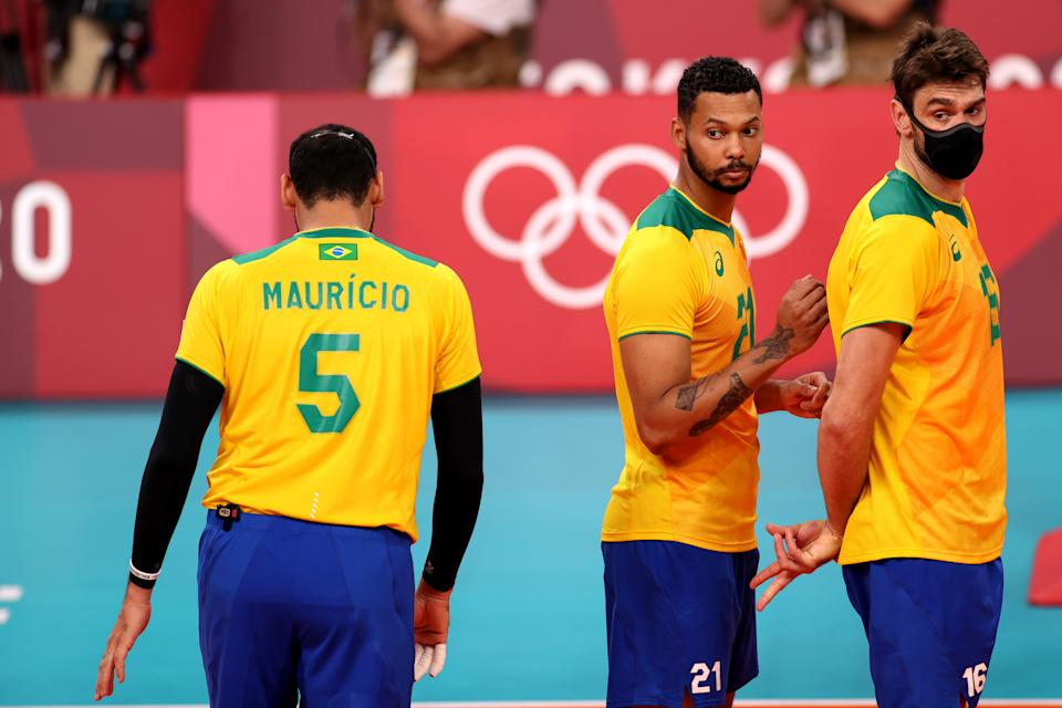 TOKYO, JAPAN - JULY 24: Mauricio Borges Almeida Silva #5 of Team Brazil gets set behind Alan Souza #21 and Lucas Saatkamp #16 prior to a serve against Team Tunisia during the Men's Preliminary Round - Pool B on day one of the Tokyo 2020 Olympic Games at Ariake Arena on July 24, 2021 in Tokyo, Japan. (Photo by Toru Hanai/Getty Images)