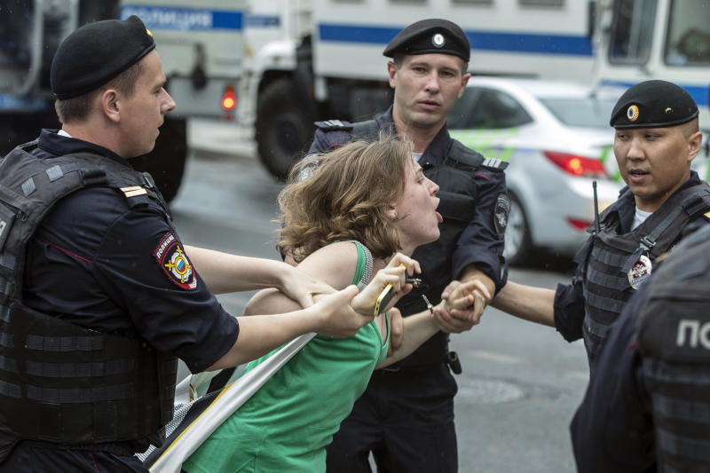 Police officers detain a woman during a march in Moscow, Russia, Wednesday, June 12, 2019. Police and hundreds of demonstrators are facing off in central Moscow at an unauthorized march against police abuse in the wake of the high-profile detention of a Russian journalist. More than 20 demonstrators have been detained, according to monitoring group. (AP Photo/Pavel Golovkin)
