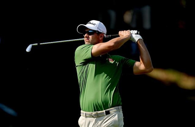 In this photo released by OneAsia, Adam Scott of Australia plays a shot during the second round of the Australian PGA Championship at the RACV Royal Pines Resort golf club on Australia's Gold Coast Friday, Nov. 8, 2013. (AP Photo/OneAsia, Khalid Redza)