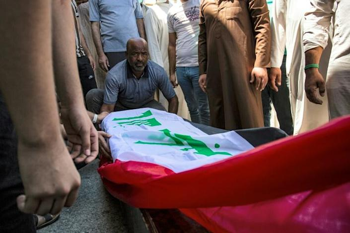 Mourners gather around the Iraqi flag draped coffin of slain activist Riham Yaaqub during her funeral in the city of Basra on Thursday