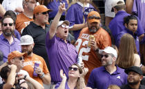 A TCU fan yells as Texas fans stand nearby during the first half of an NCAA college football game Saturday, Oct. 2, 2021, in Fort Worth, Texas. (AP Photo/Ron Jenkins)