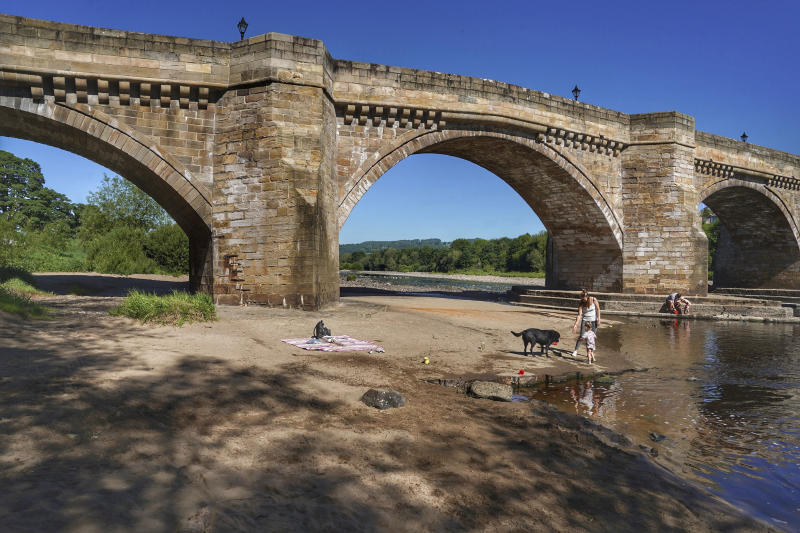 A family play in the shallows on the banks of the river Tyne, that has very low water levels, at Corbridge, England, Monday June 1, 2020.  Families who are locked down because of the coronavirus have been able to visit local beauty spots as warm weather has swept the region.  (Owen Humphreys/PA via AP)
