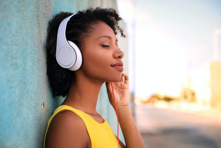A woman leaning against a wall wearing a large pair of headphones.