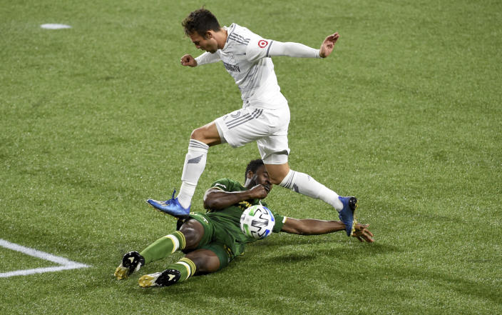 Portland Timbers defender Larrys Mabiala, bottom, slide tackles Los Angeles FC forward Danny Musovski during the first half of an MLS soccer match in Portland, Ore., Sunday, Oct. 18, 2020. (AP Photo/Steve Dykes)
