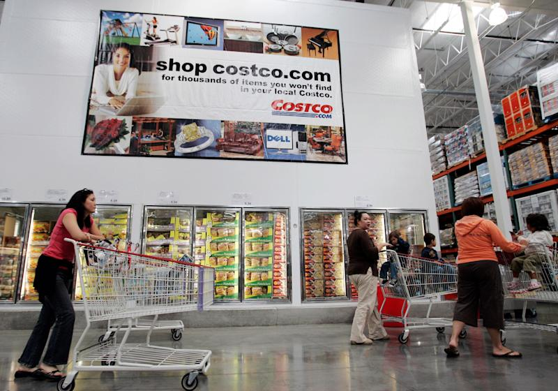 Costco shoppers walk next to an advertisement for Costco online at a Costco store in San Jose, Calif., Tuesday, Oct. 9, 2007. Shares of Costco Wholesale Corp. jumped nearly 10 percent Wednesday, Oct. 10 after the discount retailer said its fiscal fourth-quarter profit rose 5 percent on increased membership fee revenue and higher same-store warehouse sales. (AP Photo/Paul Sakuma)