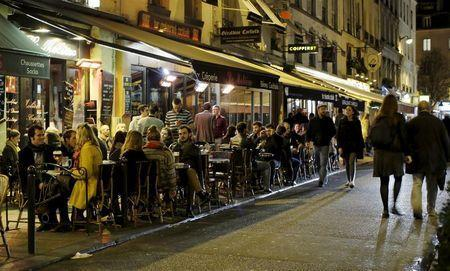 People sit at tables outside a bistro in Paris, France, November 18, 2015. REUTERS/Gonzalo Fuentes/Files