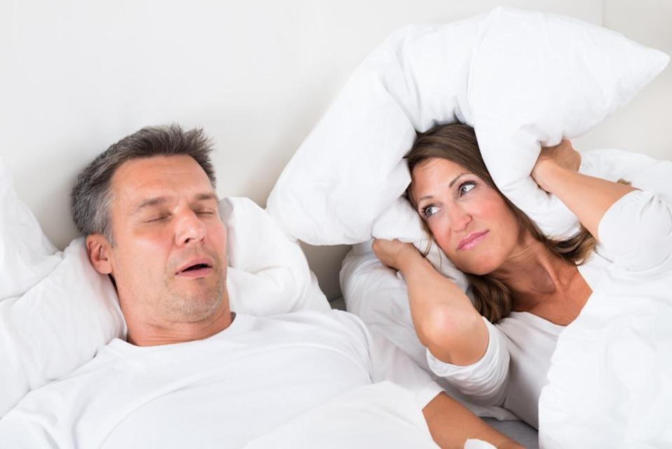 Woman Covering Her Ears With Pillow While Man Snoring