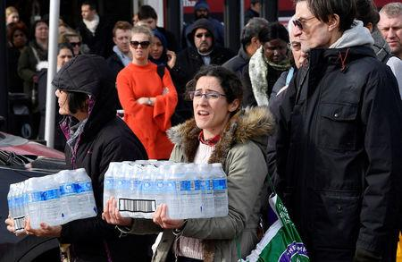 Local residents collect bottled water distributed by Thames Water after mains supplies to homes were cut off following bad weather in Balham south London