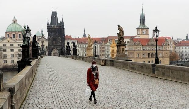 A woman wearing a face mask walks across an empty Charles Bridge in Prague on March 1 as the Czech government mandated further restrictions to curb the spread of COVID-19. The Czech Republic is one of the European Union's hardest-hit countries after initially posting the lowest number of cases as a percentage of population in the 27-member bloc. (David Cerny/Reuters - image credit)