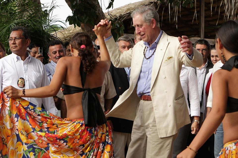<p>Prince Charles danced with locals from the Maguari Village in the Amazon Rainforest at Santaram on March 14, 2009. The trip was part of a ten-day tour of South America. <em>[Photo: Getty]</em> </p>