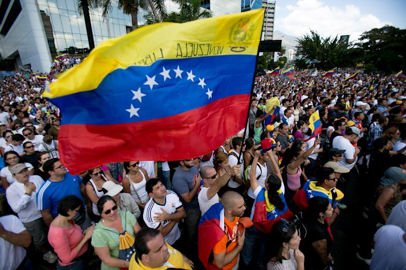 A demonstrator waves the Venezuelan flag during a protest asking for the disarmament of armed groups in Caracas, Venezuela, Sunday, Feb. 16, 2014. For the past several days, protests have rocked Caracas yielding several dead and scores of wounded in clashes between opposition protesters with security forces and pro-government supporters. (AP Photo/Alejandro Cegarra)