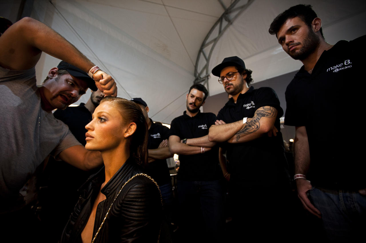 A hair stylist arranges a model's hair as other stylists watch during the preparation backstage for the catwalk presentation of summer collection designs by Lenny at Fashion Rio in Rio de Janeiro, Brazil, Friday, May 25, 2012. (AP Photo/Victor R. Caivano)