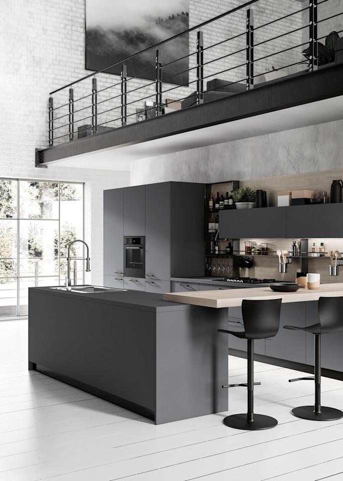 """<p>This monochrome kitchen feels incredibly spacious. The white wooden floorboards complement the matte black cabinets, while the bar area joins the workspaces together providing a space for the family to sit.<strong><br></strong></p><p><strong>READ MORE:</strong> <a href=""""https://www.housebeautiful.com/uk/decorate/kitchen/a23569477/kitchen-colour-ideas/"""">7 kitchen colour ideas</a></p><p>• Shop the look at <a href=""""http://www.scavolini.design/"""" target=""""_blank"""">Scavolini Kitchens</a></p>"""