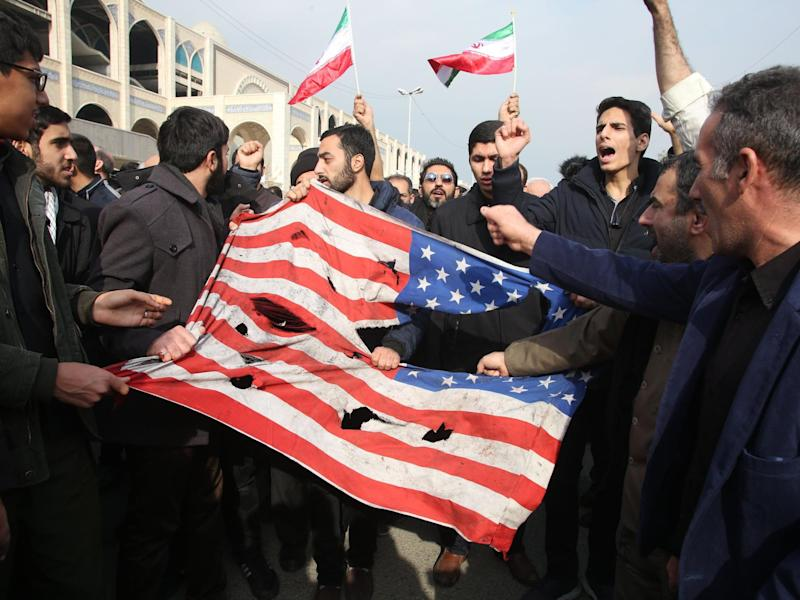 Iranians tear up a US flag during a demonstration in Tehran: AFP/Getty