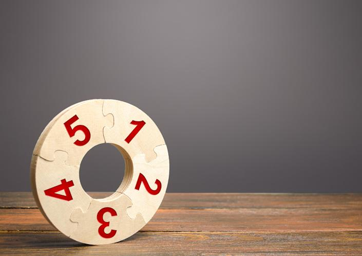Image of a numbered wooden puzzle ring on a wooden table.