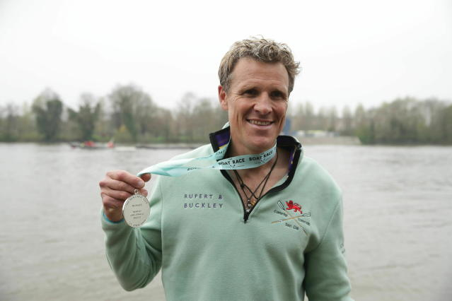 Cambridge's James Cracknell celebrates with his medal after the Men's Boat Race on the River Thames, London, Sunday, April 7, 2019. (Adam Davy/PA via AP)