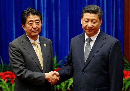 FILE PHOTO: China's President Xi Jinping shakes hands with Japan's Prime Minister Shinzo Abe during their meeting on the sidelines of the APEC meetings in Beijing