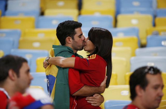 Fans kiss after the match between Spain and Chile at Maracana stadium in Rio De Janeiro June 18, 2014. Chile beat Spain 2-0. REUTERS/Jorge Silva (BRAZIL - Tags: WORLD CUP SPORT SOCCER)