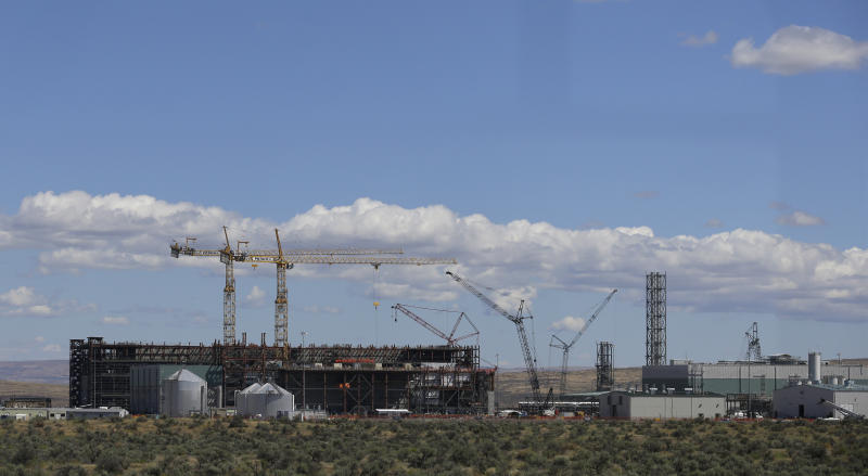 In this photo taken July 11, 2016, cranes tower above a waste treatment plant under construction on the Hanford Nuclear Reservation near Richland, Wash. The U.S. Energy Department's top official at Washington state's severely contaminated nuclear reservation says future accidental nuclear radiation releases are likely because of aging site infrastructure and inadequate cleanup funding. Hundreds were evacuated May 9, 2017 when the roof of a 1950s rail tunnel storing a lethal mix of waste from plutonium production collapsed. Tests show no radiation was released. (AP Photo/Ted S. Warren)
