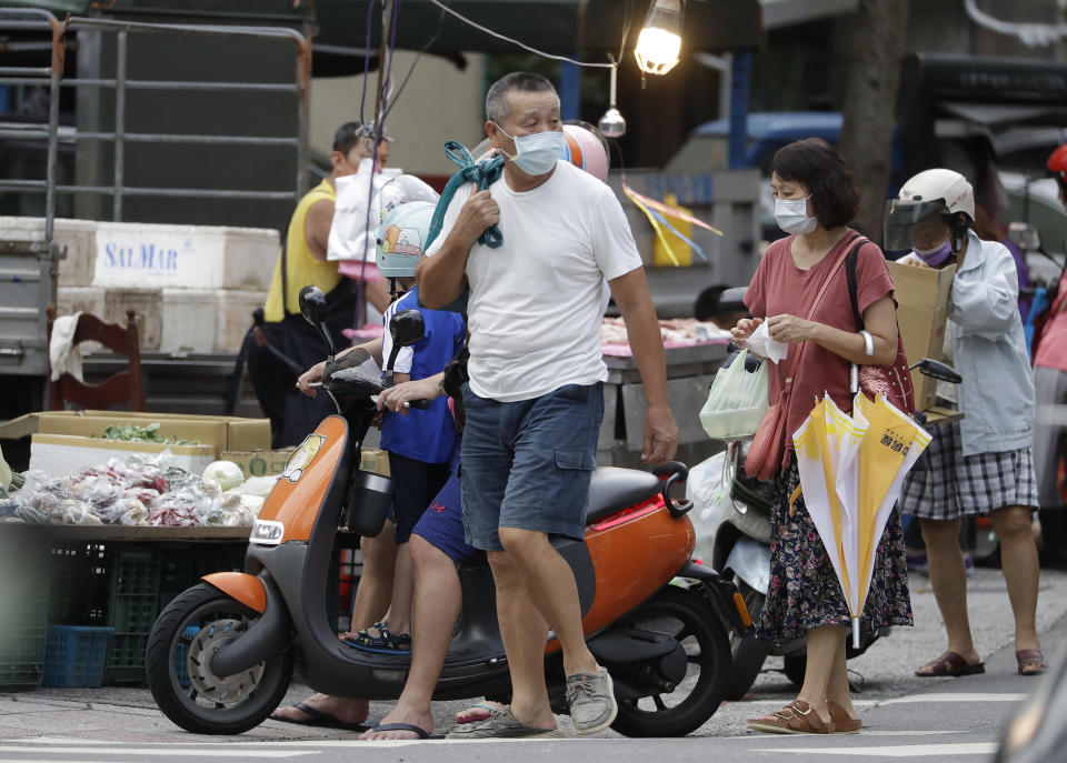 People wear face masks to help protect against the spread of the coronavirus after the COVID-19 alert rose to level 3 in Taipei, Taiwan, Friday, July 30, 2021. Taiwan's economic growth slowed to 7.5% over a year earlier in the latest quarter as anti-coronavirus controls depressed consumer spending and manufacturing. (AP Photo/Chiang Ying-ying)