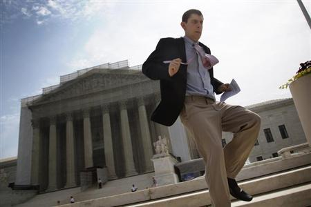 A television news producer sprints down the steps from the U.S. Supreme Court building in Washington