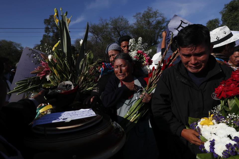 Mourners hold wreaths around the coffin of a supporter of former President Evo Morales killed during clashes with security forces in Sacaba, Bolivia, Saturday, Nov. 16, 2019. Bolivian security forces clashed with Morales' supporters in a central town Friday, leaving at least five people dead, dozens more injured and escalating the challenge to the country's interim government to restore stability. (AP Photo/Juan Karita)