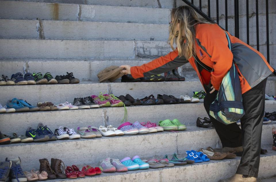 """<span class=""""caption"""">A person lays several shoes on the steps of City Hall in Kingston, Ont., to honour the 215 children's graves discovered on the grounds of the former Kamloops Indian Residential School. </span> <span class=""""attribution""""><span class=""""source"""">THE CANADIAN PRESS/Lars Hagberg </span></span>"""