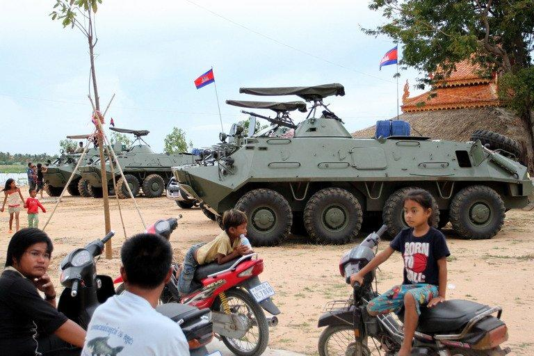 Cambodian children sit on motorbikes near armored personnel carriers on the outskirts of Phnom Penh on August 8, 2013