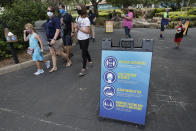 Signs remind guests of new safety measures in place at SeaWorld as it reopened, Thursday, June 11, 2020, in Orlando, Fla. The park had been closed since mid-March to stop the spread of the new coronavirus. (AP Photo/John Raoux)