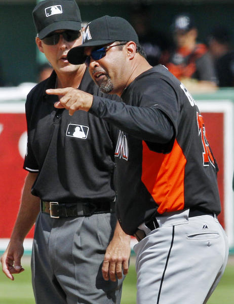 Miami Marlins manager Ozzie Guillen argues with umpire Manny Gonzalez a call in the sixth inning of a spring training baseball game against the Boston Red Sox in Fort Myers, Fla., Monday, March 12, 2012. (AP Photo/Charles Krupa)