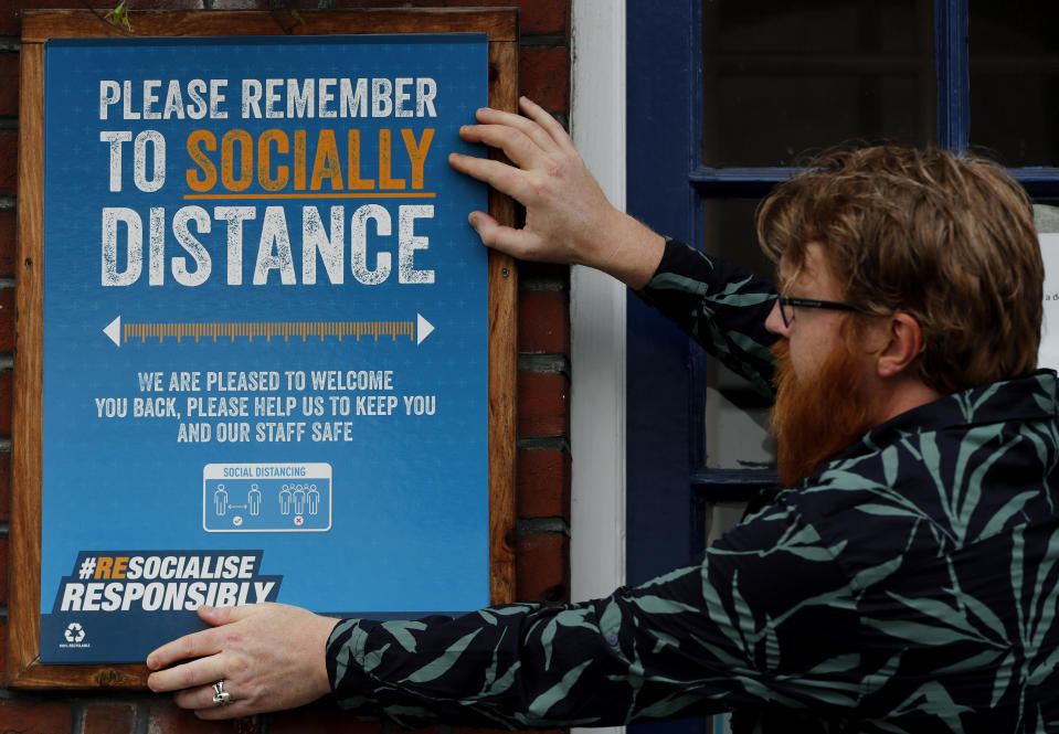 A pub owner in London puts up a sign reminding customers to obey social distancing guidelines. (AP Photo/Frank Augstein)