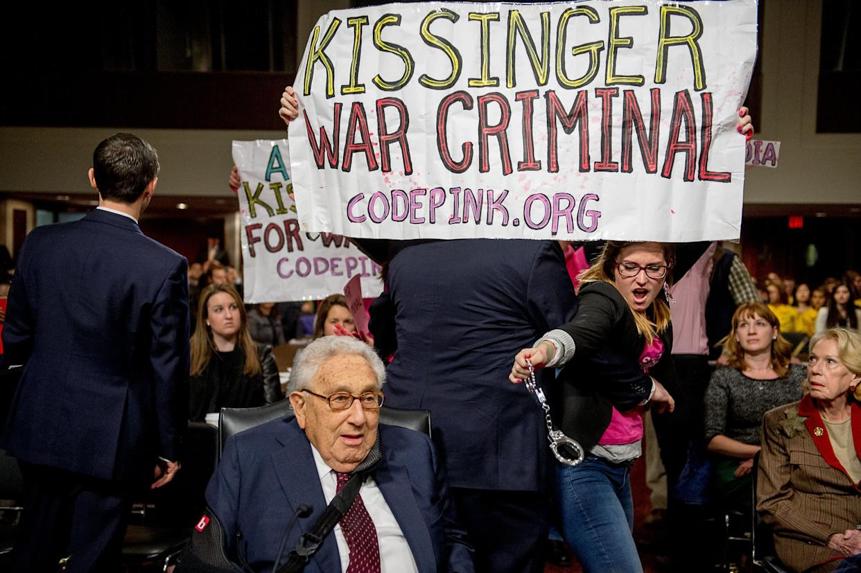 """The protest group CodePink disrupts a Senate Armed Services Committee hearing, carrying banners calling former Secretary of State Henry Kissinger a """"war criminal"""" as he and fellow former Secretary of States George Shultz and Madeleine Albright were set to testify on U.S. national security on Capitol Hill on Jan. 29, 2015."""