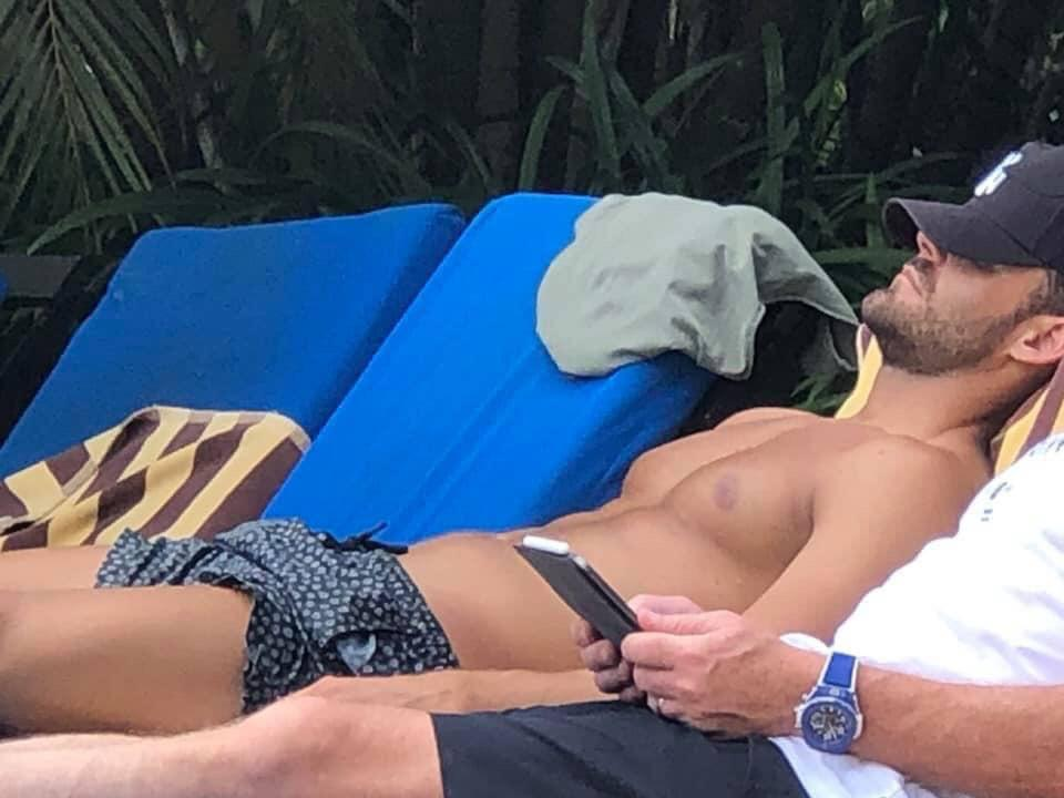 A photo of Carlin Sterritt shirtless laying by the pool in Fiji.