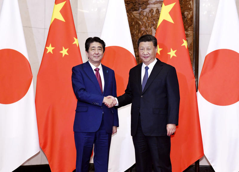 Japanese Prime Minister Shinzo Abe, left, poses with Chinese President Xi Jinping for a photo before a meeting at the Diaoyutai State Guesthouse in Beijing Friday, Oct. 26, 2018. (Kyodo News via AP)
