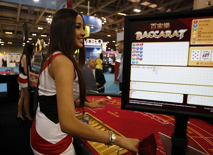 In this photo taken on Thursday, May 23, 2013, an attendant demonstrates the game of baccarat on a baccarat gaming table during the Global Gaming Expo Asia in Macau. Almost all of Macau's $38 billion in gambling revenue last year - six times more than the Las Vegas Strip - came from card game, much of it from Chinese high-rollers betting borrowed money and dwarfing the takings from slots, blackjack or roulette. Wherever you go in the former Portuguese colony, you'll see chain-smoking Chinese gamblers crowded around baccarat tables as players peel back their cards, hoping their luck will give them a good hand.(AP Photo/Kin Cheung)