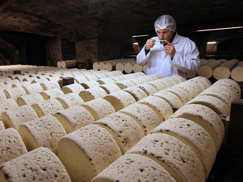 A refiner in a cellar in Roquefort, southwestern France, smells one of the village's eponymous cheeses, which could be hit by new US tariffs: AP