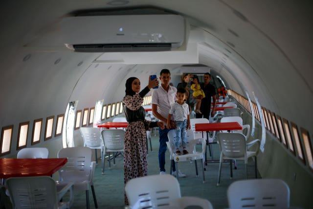 Palestinians visit the interior of a Boeing 707 after it was converted to a cafe restaurant, in Wadi Al-Badhan, near the West Bank city of Nablus