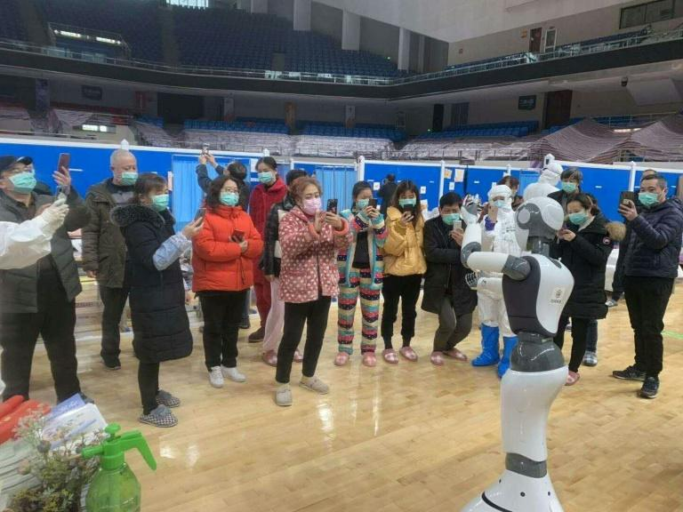 A handhout picture provided by CloudMinds shows Wuhan smart field hospital staff looking at an XR1 robot being deployed for coronavirus patient care (AFP Photo/Handout)