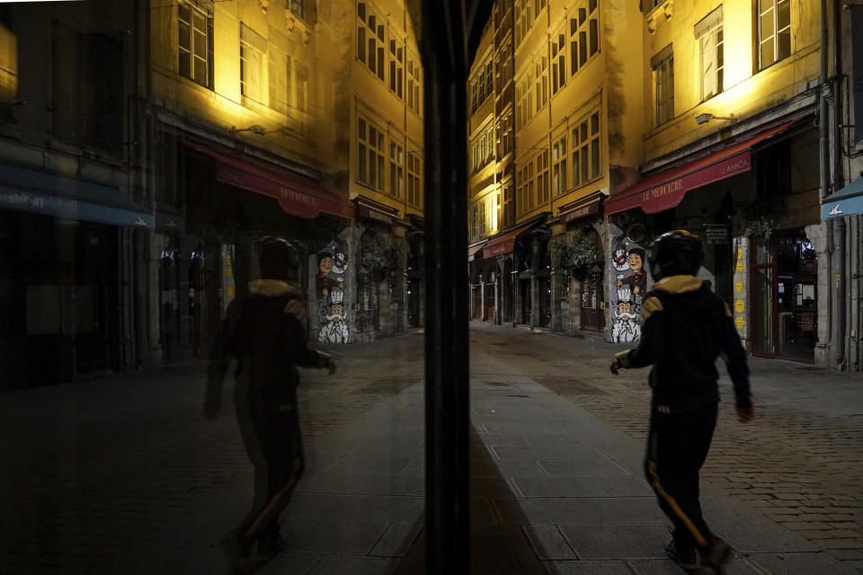 A man walks in the empty center of Lyon, central France, Saturday, Oct. 17, 2020. France is deploying 12,000 police officers to enforce a new curfew that came into effect Friday night for the next month to slow the virus spread, and will spend another 1 billion euros to help businesses hit by the new restrictions. (AP Photo/Laurent Cipriani)