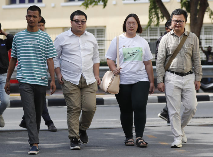 Pro-democracy activists, from left, Panupong Jadnok, Parit Chiwarak, Panusaya Sithijirawattanakul and Arnon Nampha arrive at Chana SongKhram police station in Bangkok, Thailand Monday, Nov. 30, 2020. The leaders of the pro-democracy protests reported themselves to the police for the additional charge of violating the lese majeste laws at Chanasongkram Police Station on Monday afternoon. (AP Photo/Sakchai Lalit)